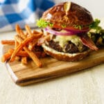 wagyu beef burger on cutting board next to sweet potato fries