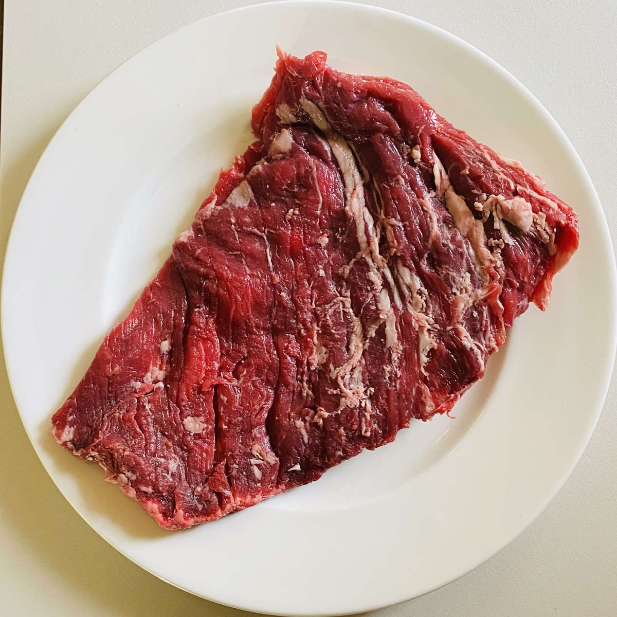 bavette steak cut raw on a white plate