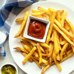 air fryer frozen french fries on a plate next to a dish of ketchup, relish and a blue napkin