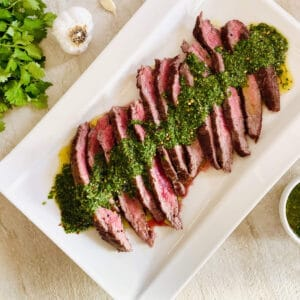 sliced bavette steak on plate topped with chimichurri