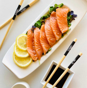 salmon sashimi on a bed of microgreens garnished with lemon next to soy sauce and chopsticks