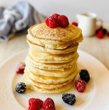 almond milk pancakes in a stack on a plate topped with raspberries