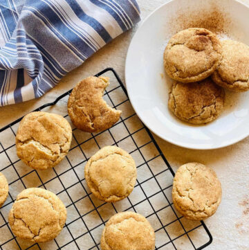snickerdoodle recipe without cream of tartar on white plate with tray of snickerdoodle cookies in background