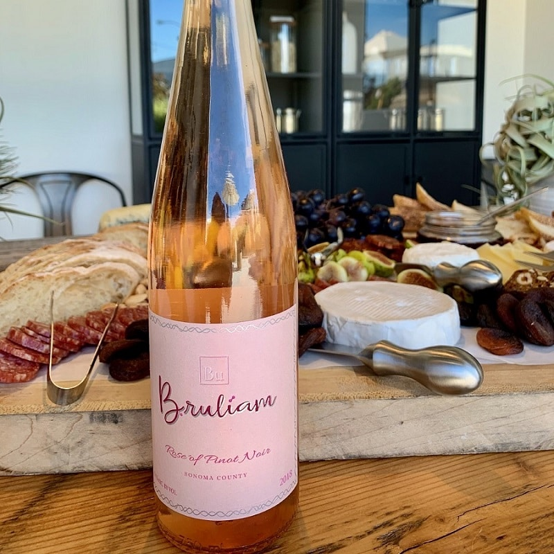 bruliam wine with charcuterie board in background