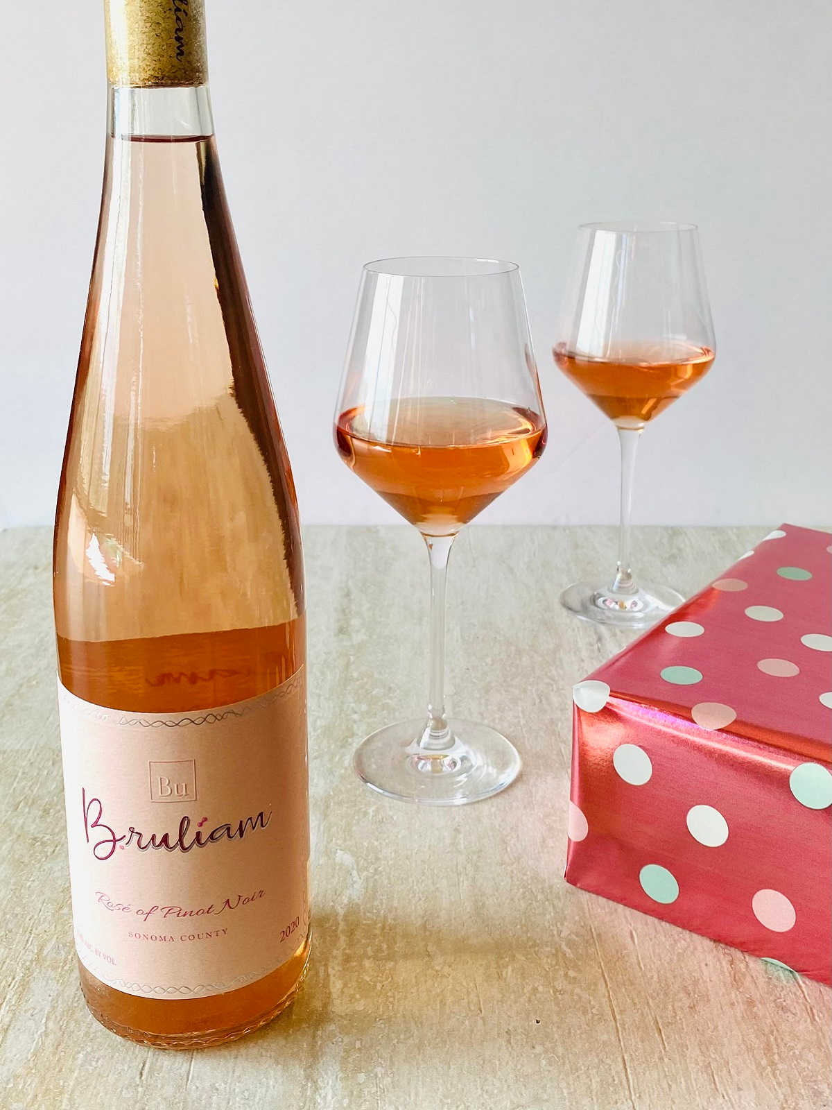 bottle of bruliam wine next to 2 glasses of wine and a wrapped pink present