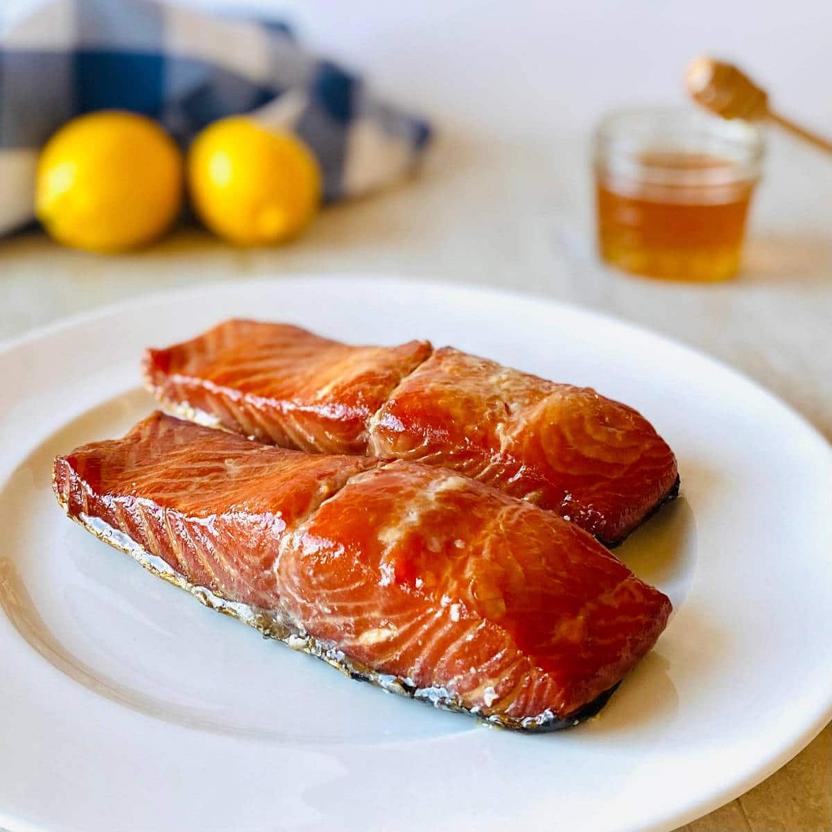 honey glazed smoked salmon on a plate with honey and lemons in the background