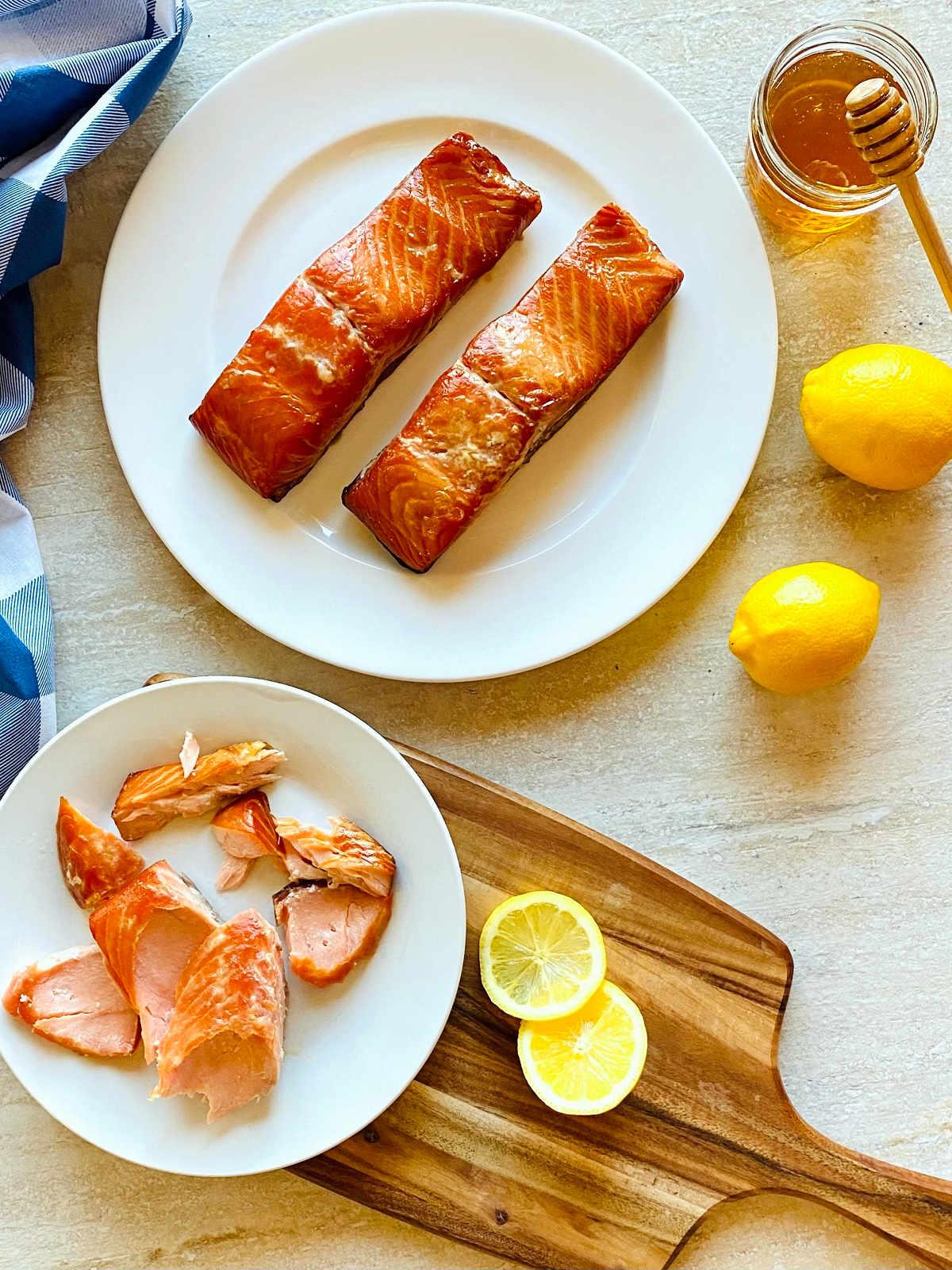 honey smoked salmon on a plate next to honey and lemons