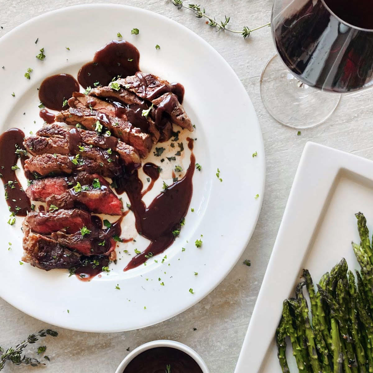 wagyu ribeye steak covered in wagyu bacon bordelaise sauce next to glass of red wine and asparagus