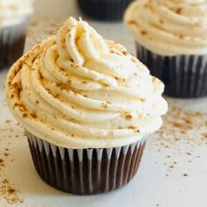 a chocolate cupcake with cream cheese frosting no butter and other cupcakes in the background