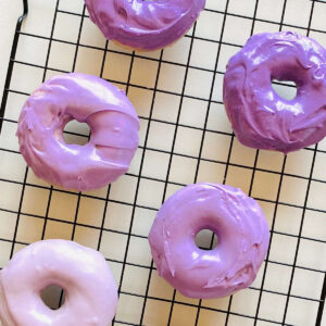 ube donuts on a cooling rack