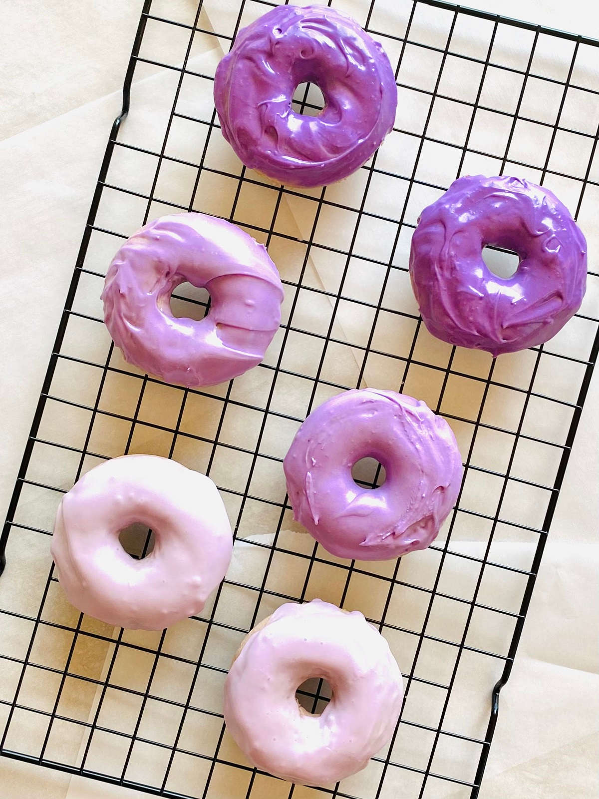 ube donuts on a black cooling rack