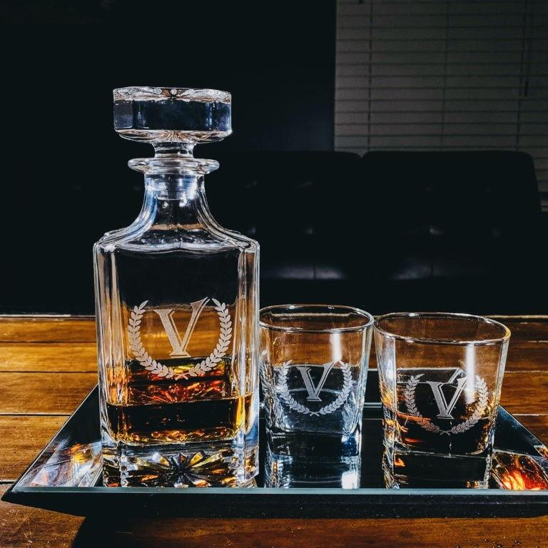 engraved decanter set next to two rocks glasses