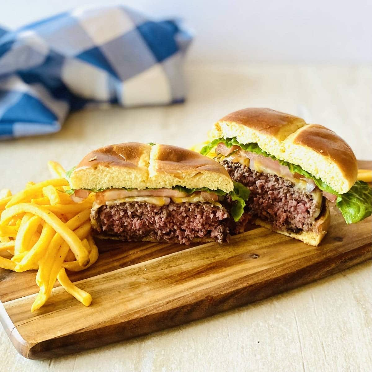 elk burgers cut in half on a wooden platter next to french fries