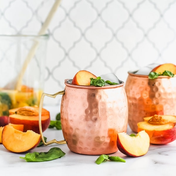 2 moscow mule copper cups surrounded by basil and peaches