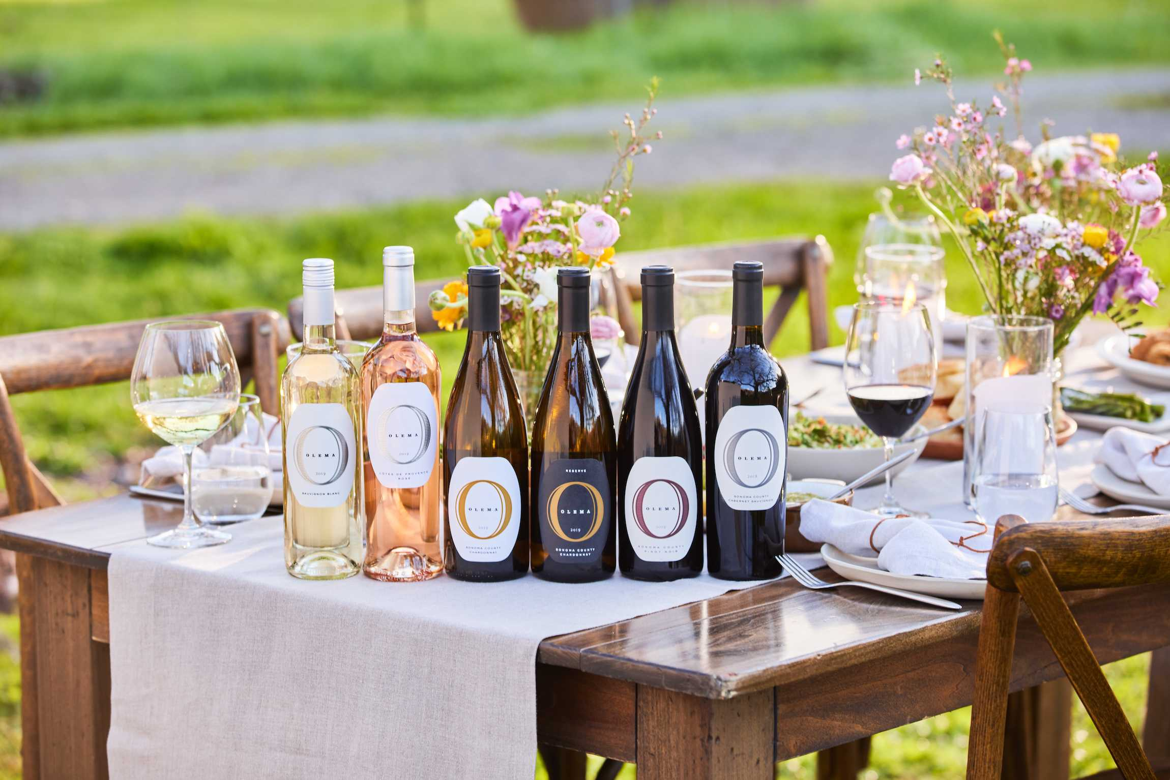 a variety of olema wines sitting on a table with wines glasses and flowers