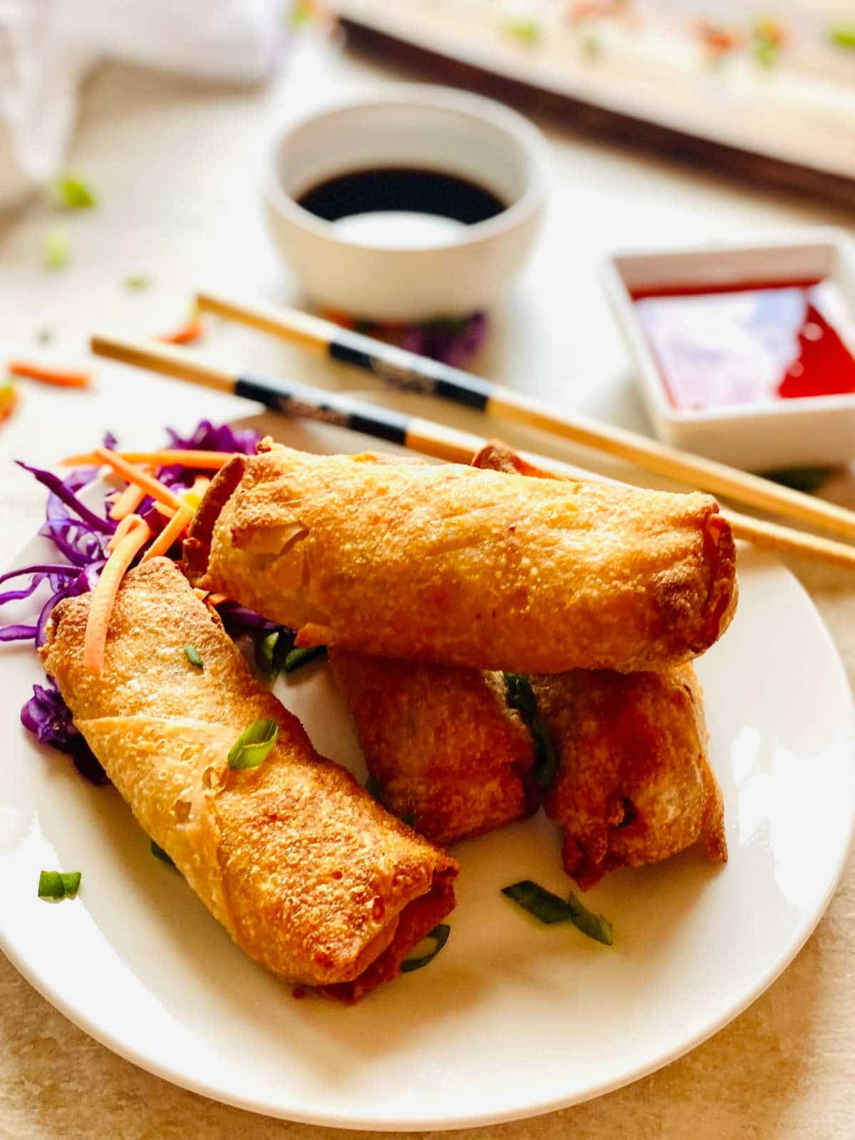 air fryer frozen egg rolls on a plate next to chopstick, soy sauce and thai chili dipping sauce