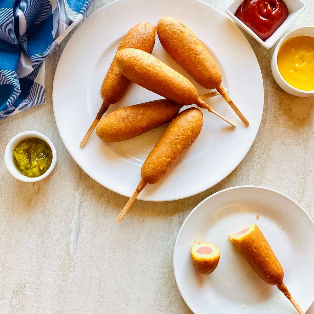frozen air fryer corn dogs on a plate next to ketchup, mustard and relish