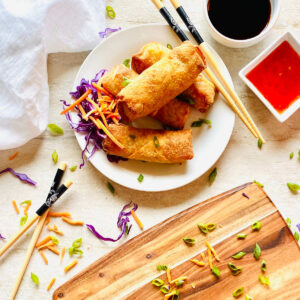 frozen egg rolls cooking in air fryer on a plate next to chopstick, soy sauce and thai chili dipping sauce