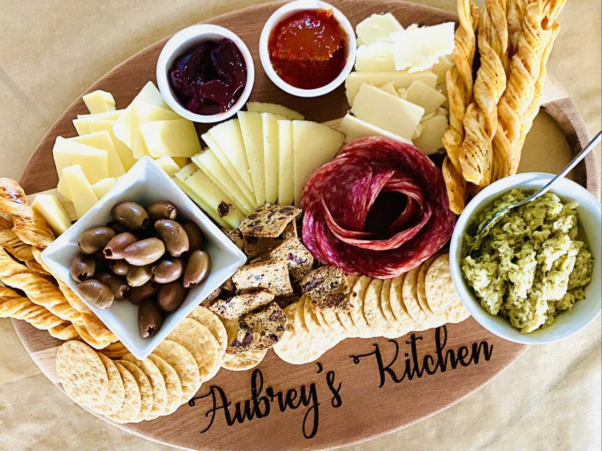 charcuterie with salami rose, olives, meats cheese, dips and artichoke spread
