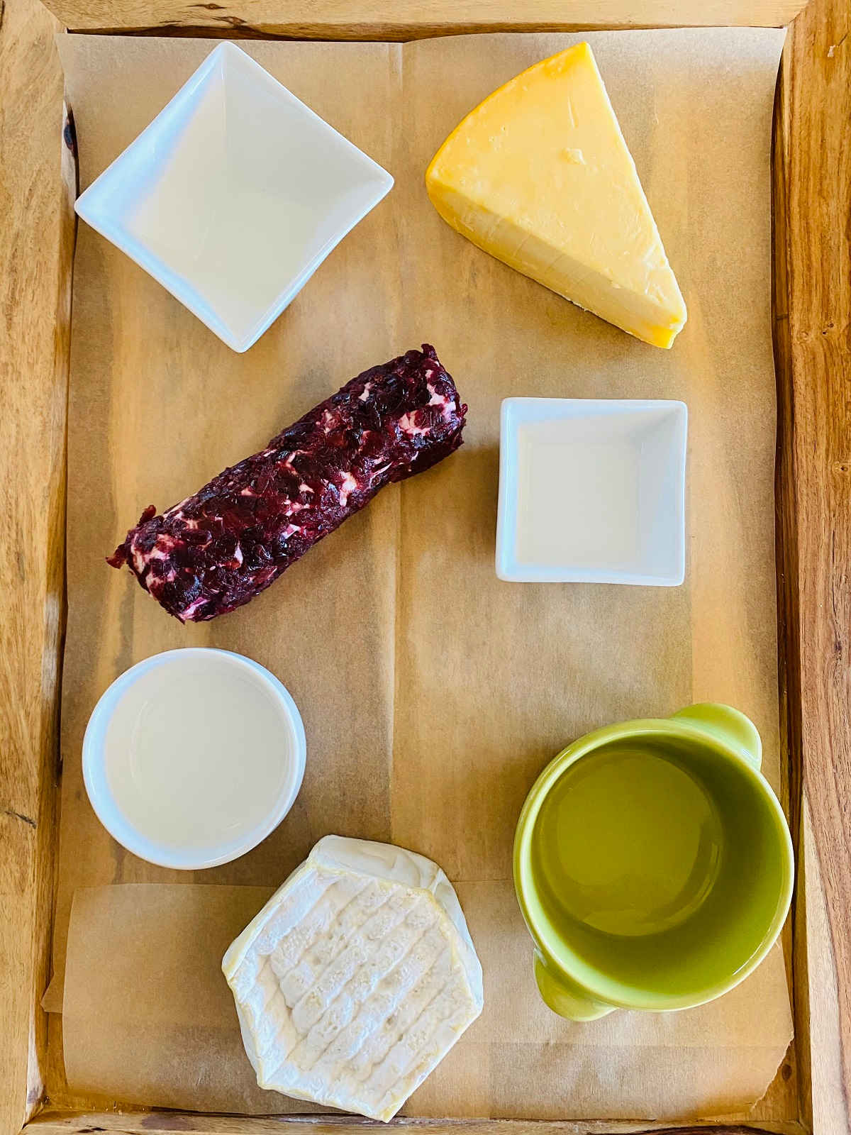 charcuterie board with bowls and two cheeses assembled