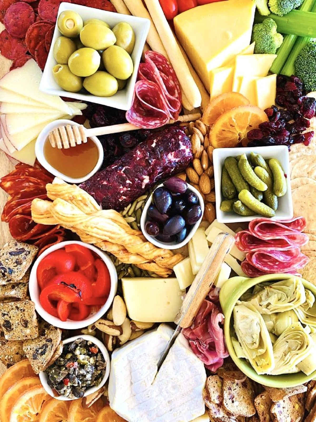trader joe's charcuterie board with honey pickles red peppers vegetables nuts fruits cheese meat and dips and spreads