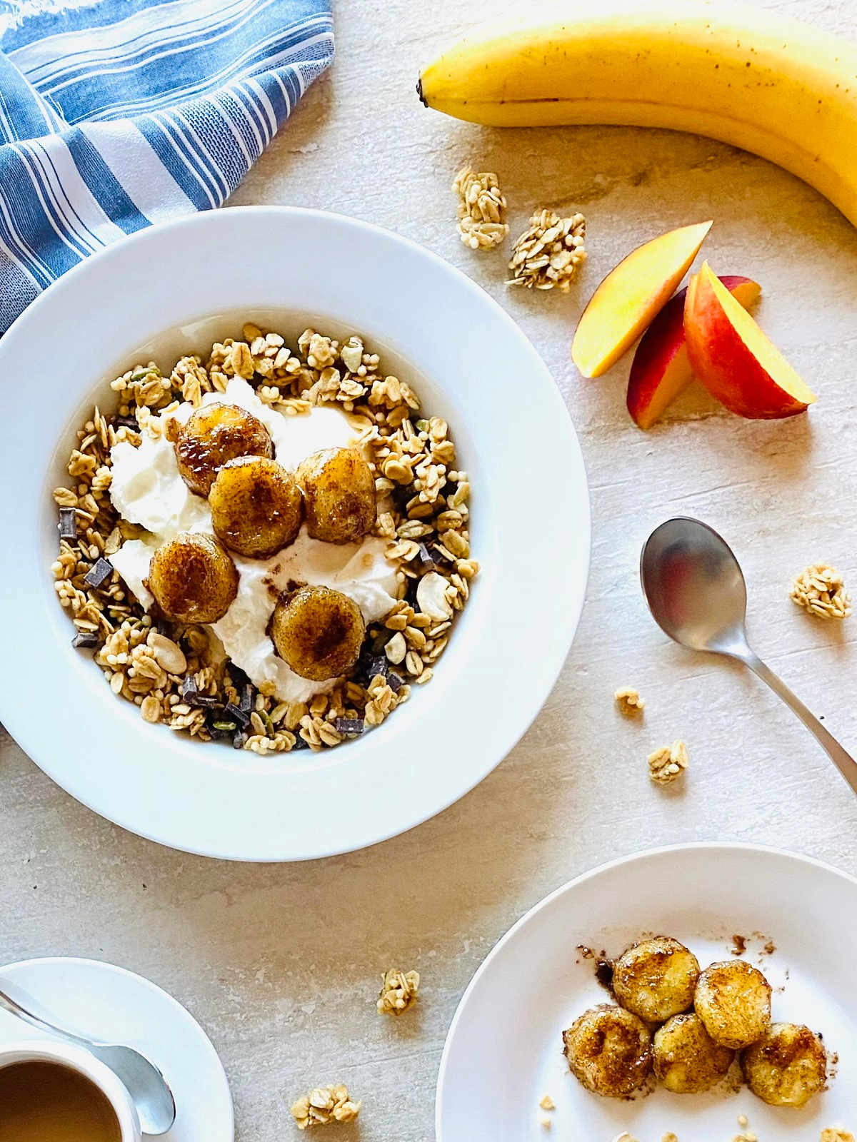 air fryer caramelized bananas in a bowl with yogurt and granola next to bananas and nectarines