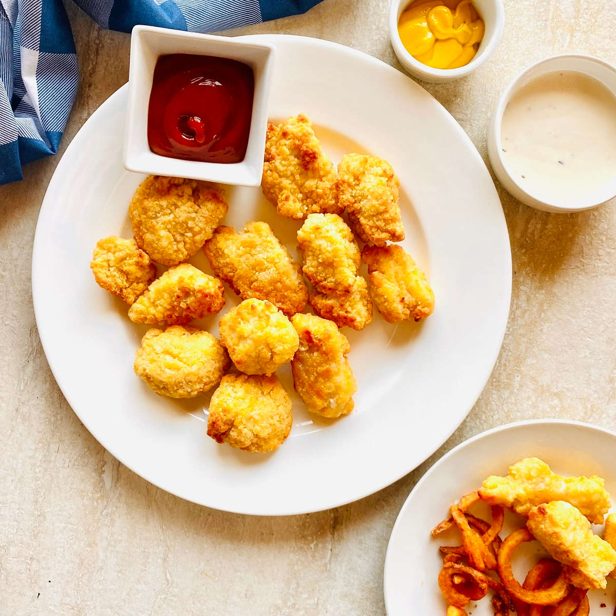 frozen chicken nuggets cooked in air fryer on a plate with ketchup and mustard for dipping