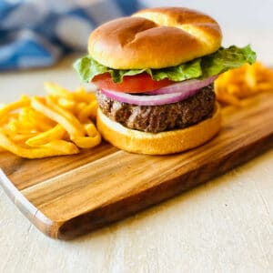 hamburger cooked frozen in air fryer on a cutting board with french fries