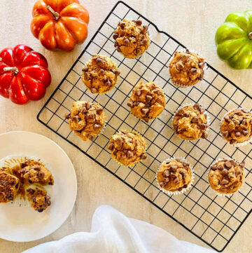 3 ingredient pumpkin chocolate chip muffins on a baking rack next to colored pumpkins