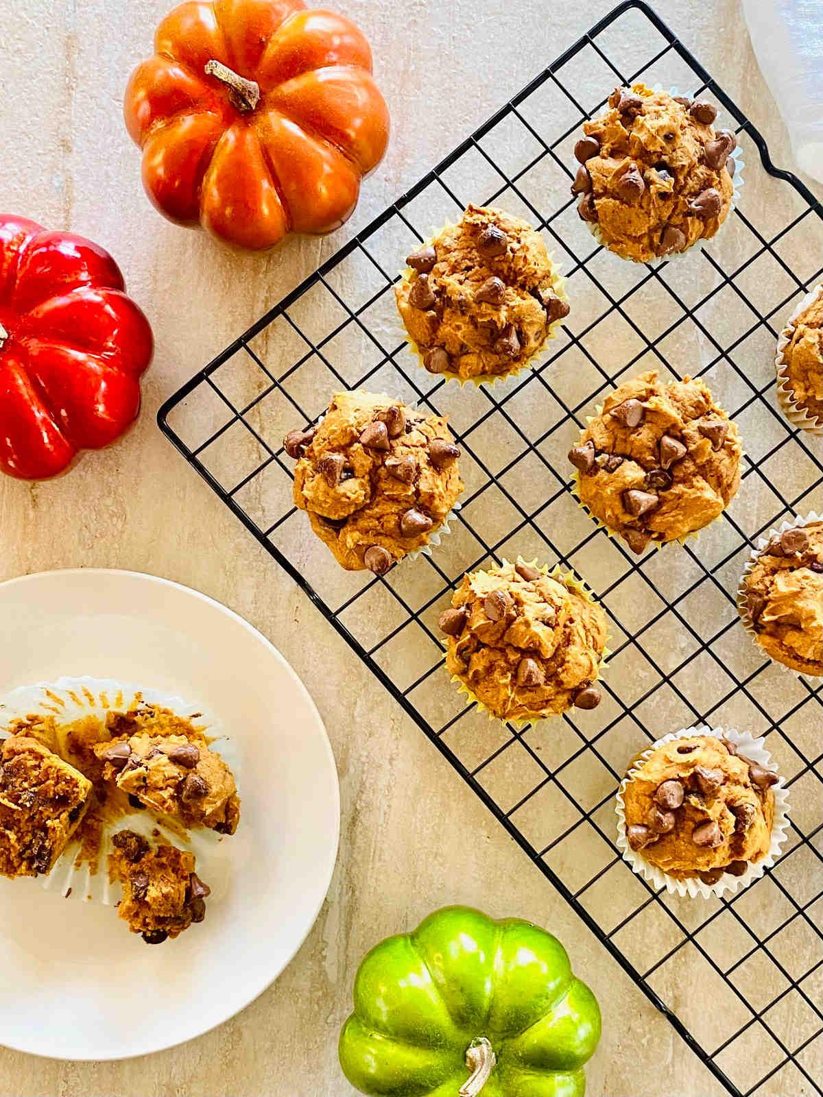 3 ingredient pumpkin muffins on a baking rack next to colored pumpkins