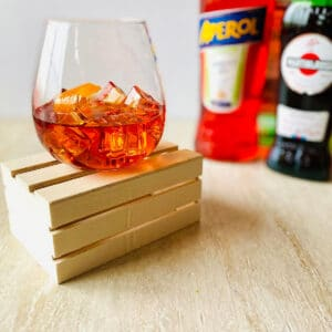 Aperol Negroni cocktail in a glass with ice, an orange peel and aperol, vermouth and gin in the background