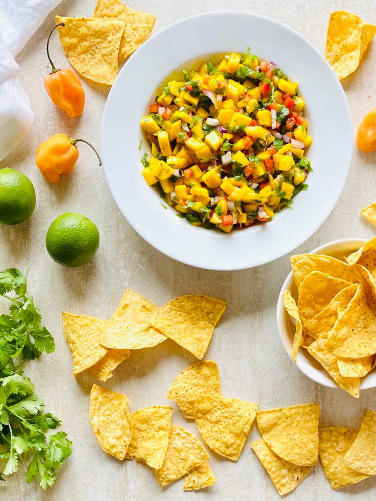 habanero mango salsa in a bowl surrounded by chips, habanero peppers, limes and cilantro