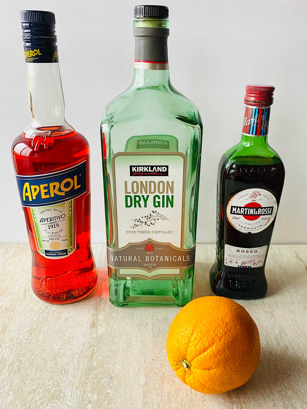 a bottle of aperol, gin, vermouth and an orange, ingredients to make aperol negroni