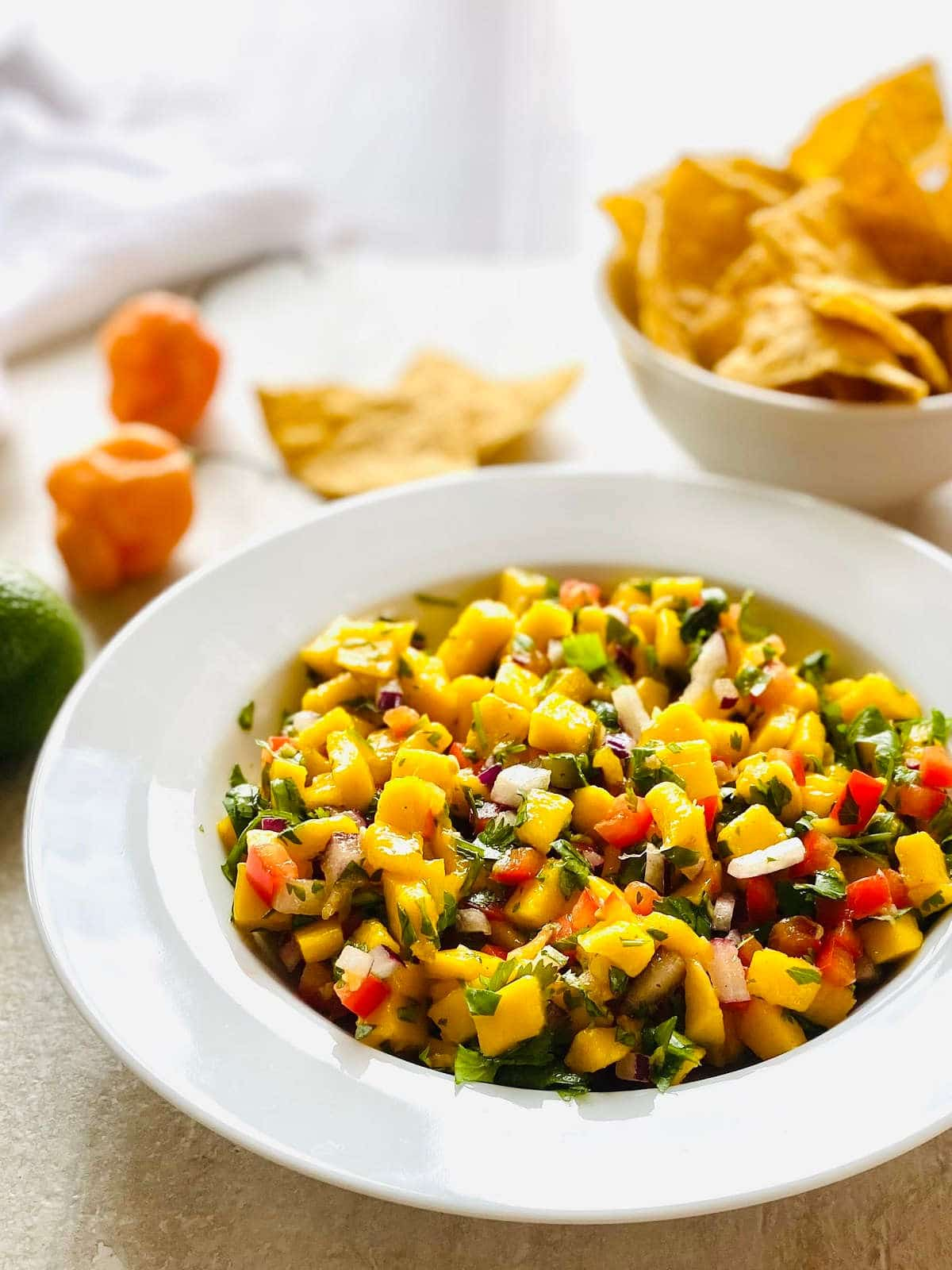 habanero mango salsa in a bowl and a bowl of tortilla chips and habanero peppers in the background