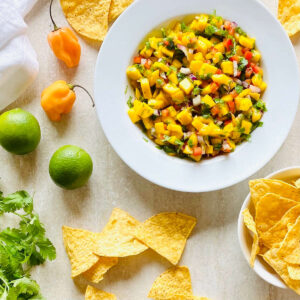 mango habanero salsa in a bowl surrounded by chips, habanero peppers, limes and cilantro