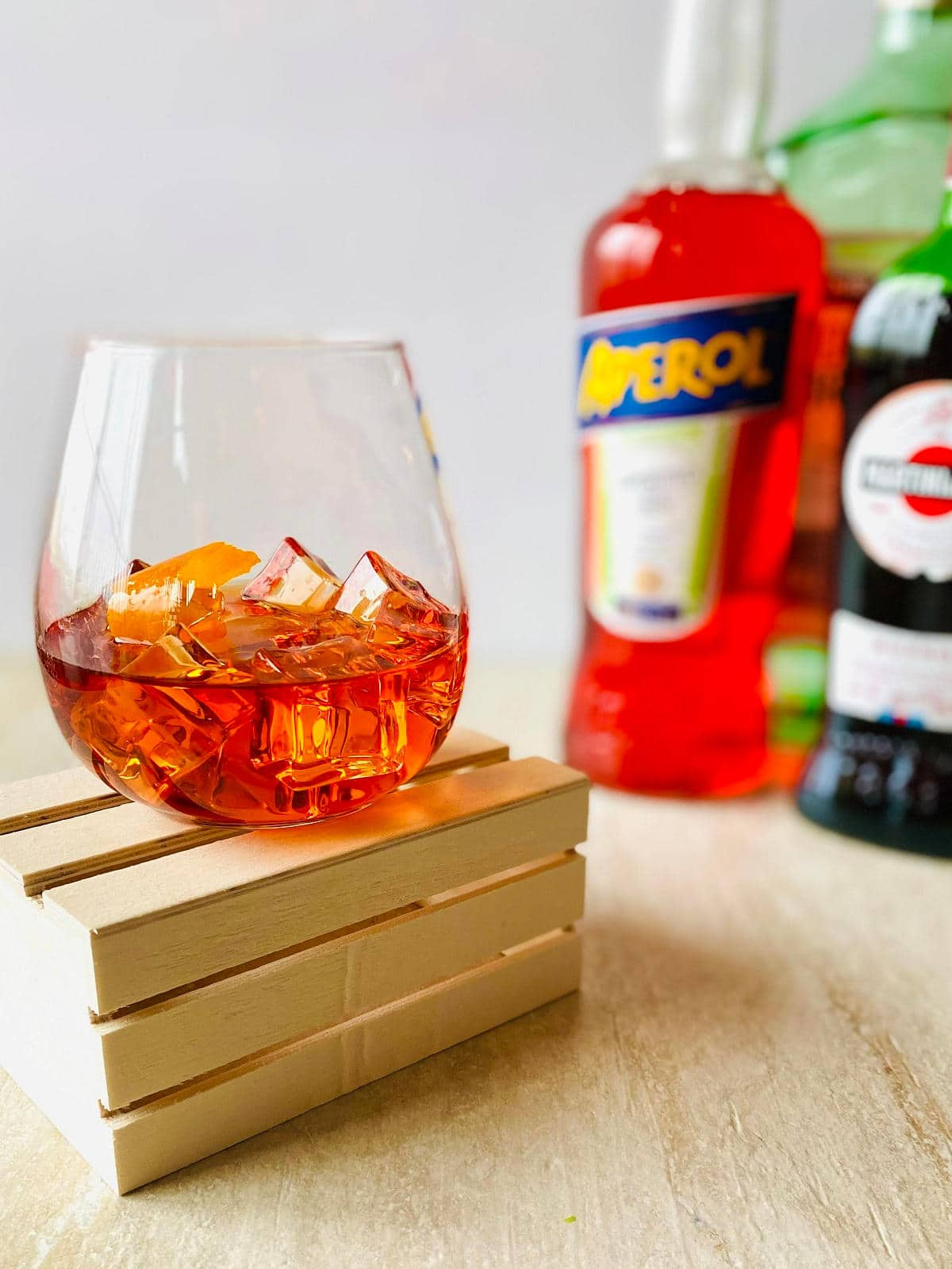 negroni with aperol cocktail in a glass with ice, an orange peel and aperol, vermouth and gin in the background