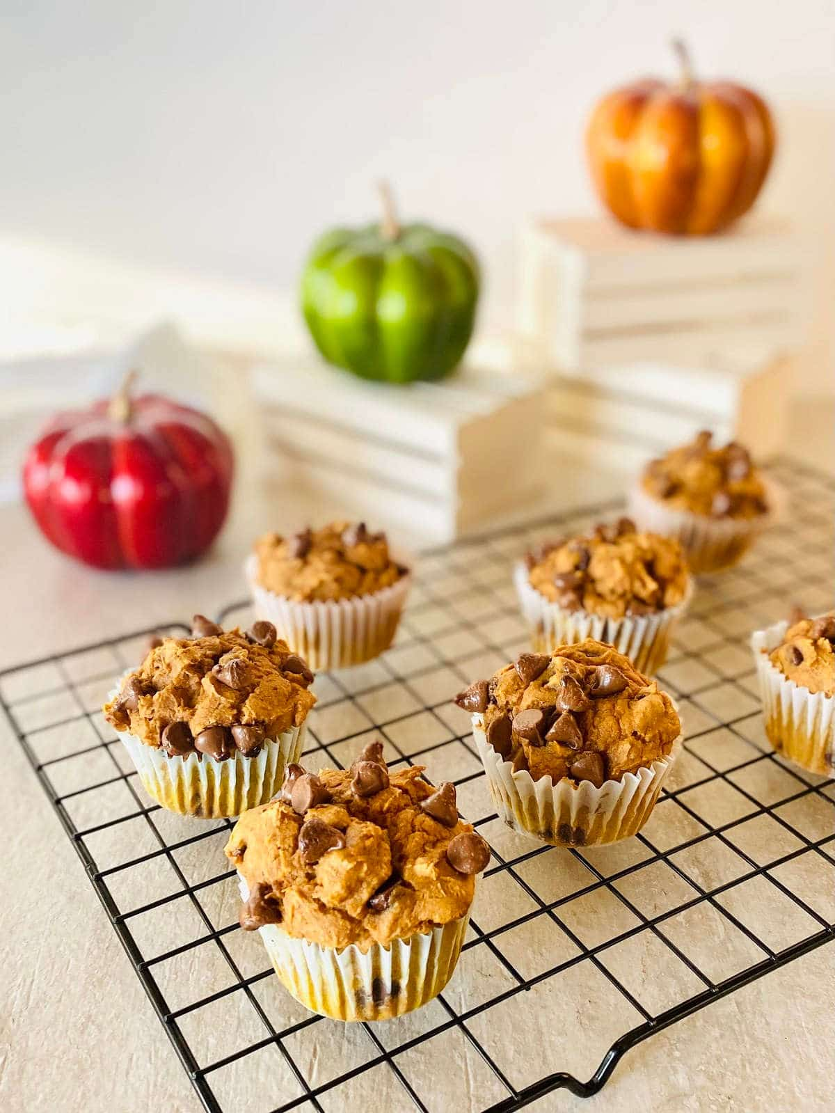 three ingredient pumpkin muffins on a baking rack with pumpkins in the background