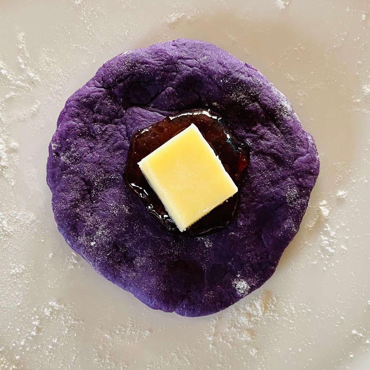 ube cheese pandesal dough with halaya jam and cheese on top