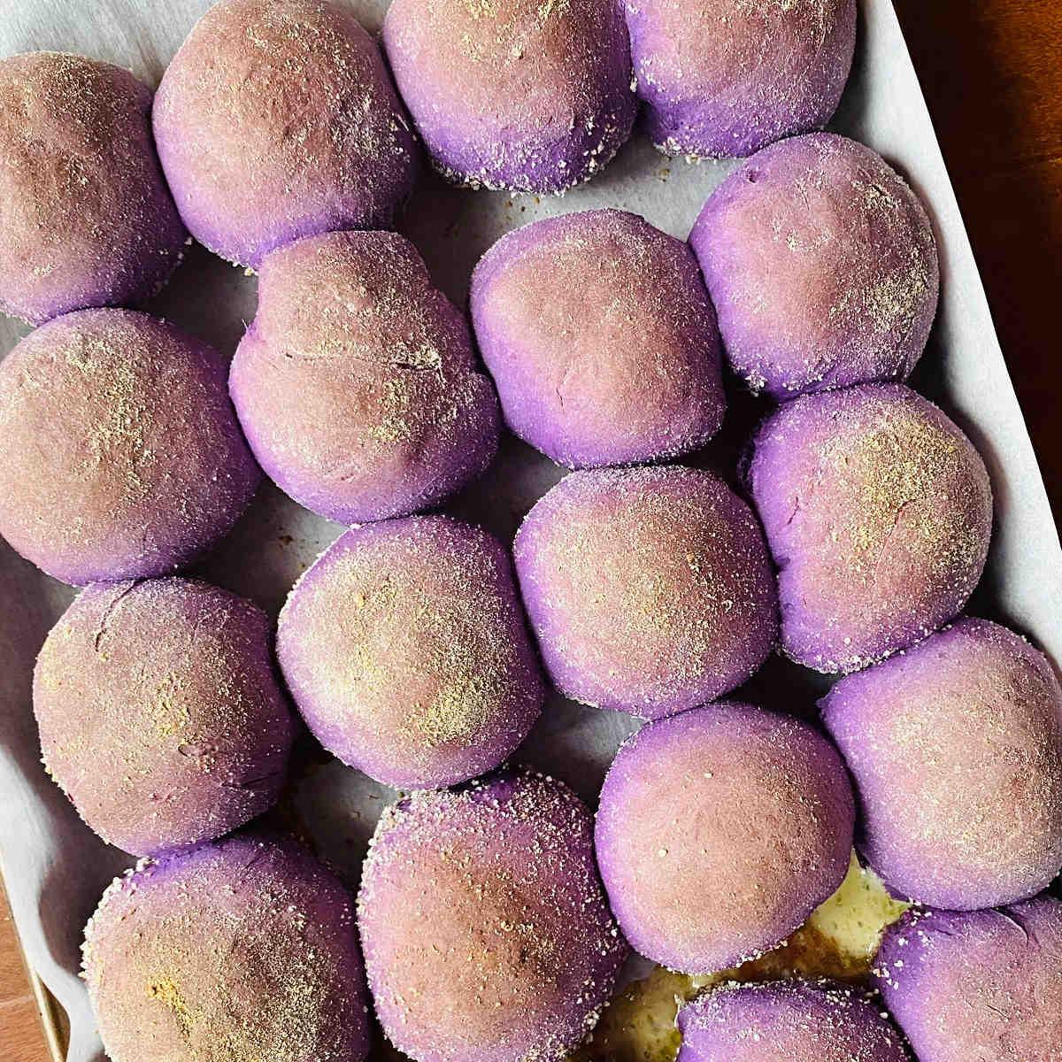 freshly baked ube pandesal rolls on baking sheet